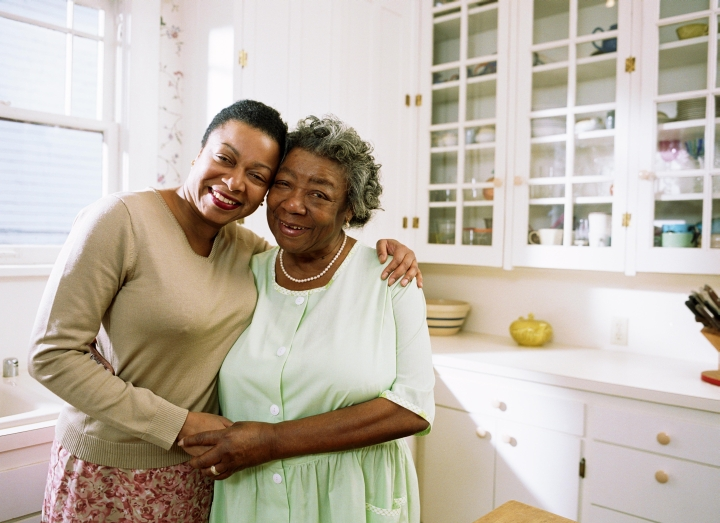 Woman and Mature Woman Hugging in the Kitchen